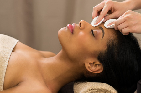 massage: Junge Frau mit Make-up Gesicht mit Wattestäbchen entfernt