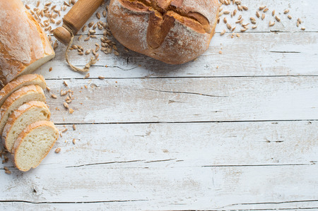 Loafs of bread and rolling pin on rustic table with grain Foto de archivo