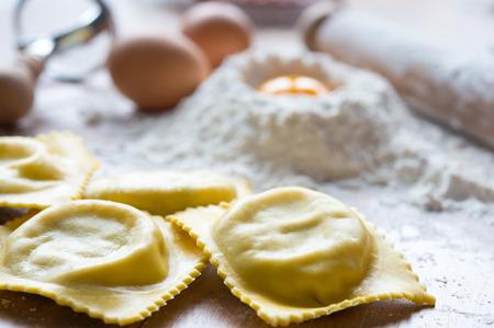 Verse zelfgemaakte Italiaanse pasta gevuld met kaas en spinazie op tafel