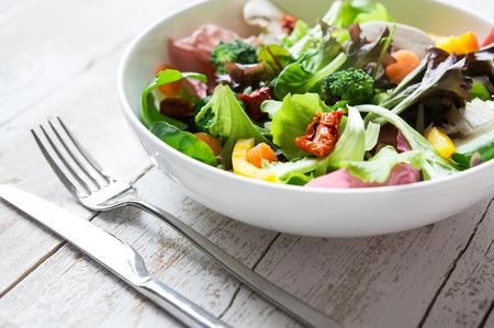 comidas saludables: Cerca de la taza con ensalada mixta en la mesa rústica Foto de archivo