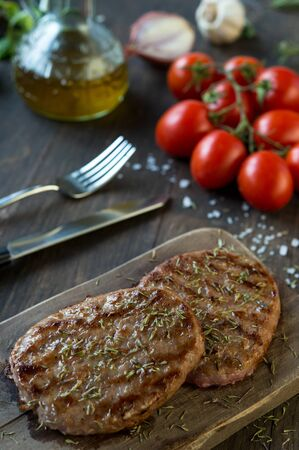 hamburger steak: Grilled beef hamburgers on rustic cuttind board with oil and tomato Stock Photo