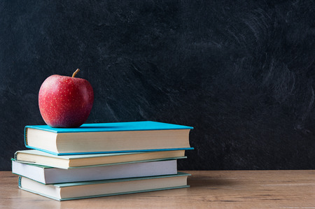 Apple and a stack of books on desk with blackboard in background Stock Photo