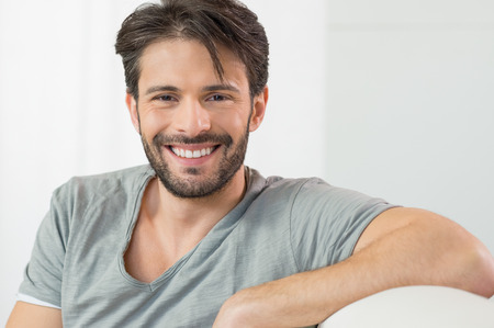 Portrait of smiling man looking at camera sitting on couch Foto de archivo
