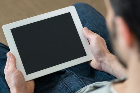 Gros plan d'un homme tenant tablette numérique assis sur le canapé