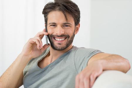 Porträt der lächelnden Mann im Gespräch über Handy zu Hause Standard-Bild