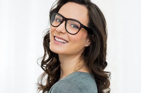 Closeup of smiling young woman looking at camera with eyeglasses
