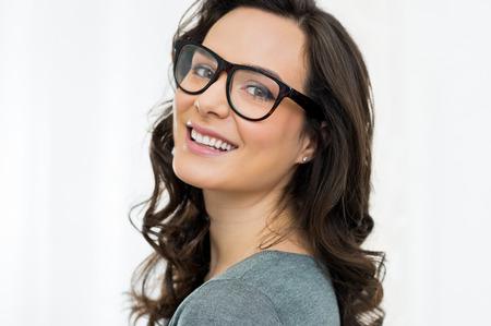 Gros plan de sourire jeune femme regardant la caméra avec des lunettes