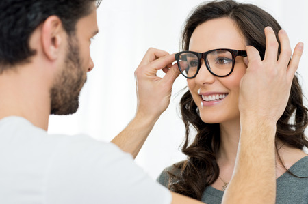 optician: Optician putting a new pair of eyeglasses on a patient
