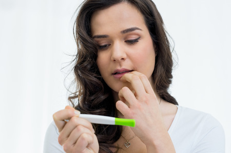 Portrait of worried young woman waiting for the result of the pregnancy test Stockfoto