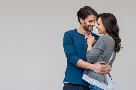 parejas jovenes: Pareja feliz abrazando contra el fondo gris Foto de archivo