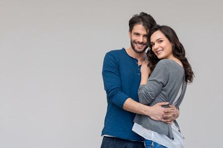 parejas felices: Retrato de pareja feliz mirando a la cámara contra el fondo gris