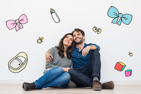 Portrait of happy young couple sitting against a white wall and dreaming to have a baby and a family. Their dreams are sketched with colors on the wall. They are a young hispanic couple dressed in casual clothes.