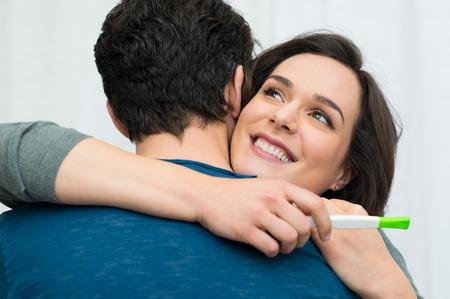 prueba de embarazo: Detalle de feliz hombre abrazando mujer joven después de la prueba de embarazo positiva
