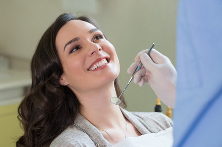 young man smiling: Closeup of dentist examining young womans teeth Stock Photo