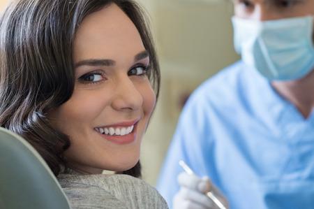 Lächelnde junge Frau, die zahnärztliche Kontrolluntersuchung Standard-Bild