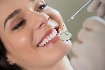 検討の若い女性の歯の歯科医のクローズ アップ 写真素材