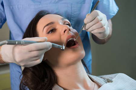 dentist drill: Closeup of dentist examining young womans teeth Stock Photo