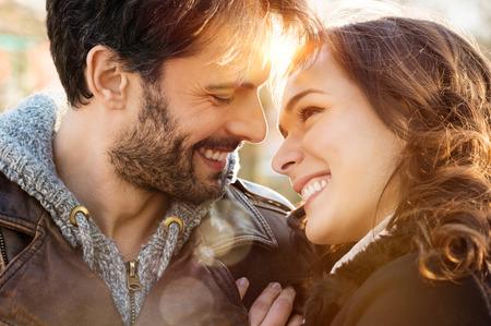 parejas enamoradas: Retrato de la joven pareja feliz mirando el uno al otro y sonriendo al aire libre