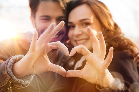 Close up de casal fazendo forma de coração com as mãos Imagens