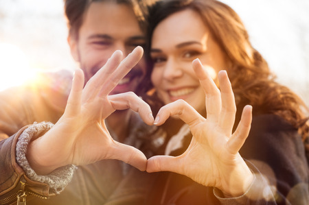 romantic couples: Closeup of couple making heart shape with hands