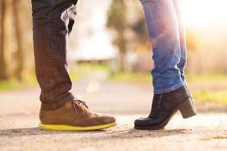 man woman kissing: Closeup of woman standing on tiptoe with man Stock Photo