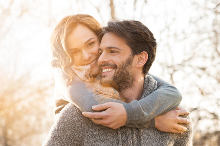 adult couple: Closeup of smiling man carrying woman piggyback outdoor Stock Photo
