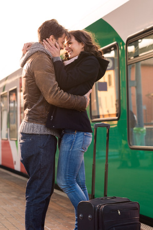 station: Happy couple embracing on railway station platform Stock Photo