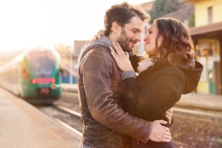 parejas romanticas: Pares felices que abrazan en la plataforma de la estación de tren