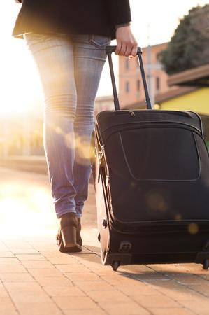 wheeling: Woman wheeling suitcase on railway station platform
