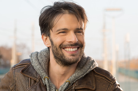 Closeup of smiling man looking away outside Foto de archivo