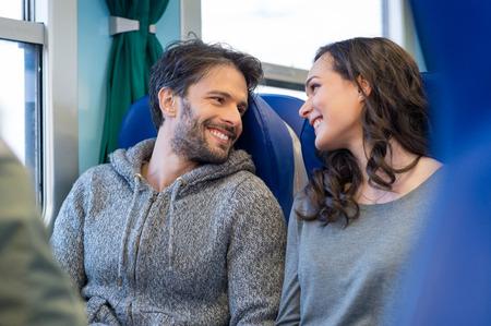 旅遊: 特寫幸福的年輕夫婦坐火車一起旅行。他們都看著對方,同時面帶微笑,享受旅行。他們坐在藍色的座位在火車的教練。