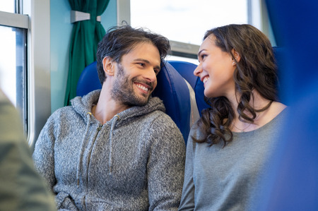 Primer plano de la feliz pareja joven que viaja en tren juntos. Ellos están buscando el uno al otro mientras sonriente y disfrutar del viaje. Son sentarse en los asientos azules en entrenador de un tren. Foto de archivo