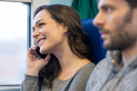 people travelling: Portrait of a happy young woman talking on telephone whiel travelling on train. She is looking away and out of the window. She is smiling and near her boyfriend. Stock Photo
