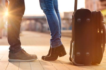 viagem: Close up disparado de pés da mulher em pé na ponta dos pés, enquanto abraçando o homem na plataforma ferroviária para uma despedida antes da partida do trem. A bagagem viajar é em primeiro plano. Bela luz do sol quente e alargamento está vindo do fundo.