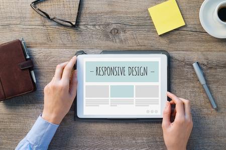 Detailní záběr na digitální tablet s responive designu webové stránky. Žena ruce jsou asi surfovat na webovou stránku. Moderní prostředí s dřevěným stolem a kancelářských objektů.