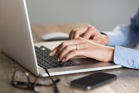 Plan Gros plan d'une femme en tapant des mains sur le clavier de son ordinateur portable. Secrétaire travaillant dans le bureau à la réception. Faible profondeur de champ avec un accent sur la saisie sur le clavier de l'ordinateur portable.