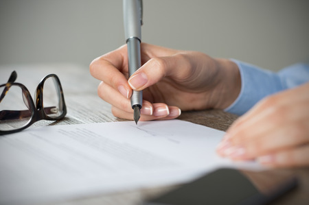 documents: Closeup shot of a woman signing a form. Businesswoman signing a new agreement at office. Shallow depth of field with focus on tip of the pen.
