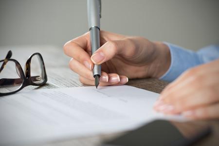 contrato de trabajo: Primer disparo de una mujer de firmar un formulario. Empresaria que firma un nuevo acuerdo en la oficina. Poca profundidad de campo con enfoque en la punta de la pluma. Foto de archivo