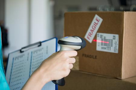 Close-up shot van de werknemer scanning doos met barcode-lezer. Lezen en scannen labels op de dozen met bluetooth barcode scanner in een magazijn. Ondiepe scherptediepte met focus op het scannen doos met barcode-lezer.