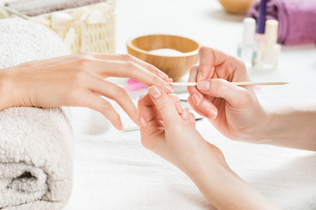 Closeup shot of a woman using a cuticle pusher to give a nail manicure. Nail technician giving customer a manicure at nail salon. Young caucasian woman receiving a french manicure. Foto de archivo