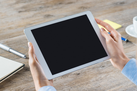 Closeup shot of a woman hand holding digitaltablet. Business woman showing a digital tablet with black screen in her office. Blank screen to put it on your own web page design.