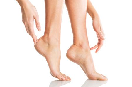 Gros plan d'une femme application de crème hydratante à la jambe et des pieds. pieds de beauté et les mains isolés sur fond blanc. Jeune femme de toucher avec les mains et les jambes ongles manucurés français. Banque d'images