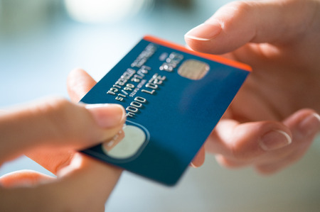 Closeup shot of a woman passing a payment credit card to the seller. Girl holding a credit card. Shallow depth of field with focus on the credit card. Stock Photo