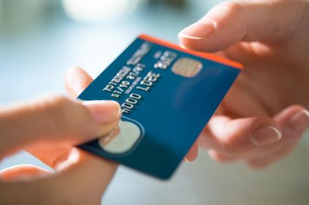 Gros plan d'une femme en passant une carte de crédit de paiement pour le vendeur. Fille tenant une carte de crédit. Faible profondeur de champ avec un accent sur la carte de crédit. Banque d'images