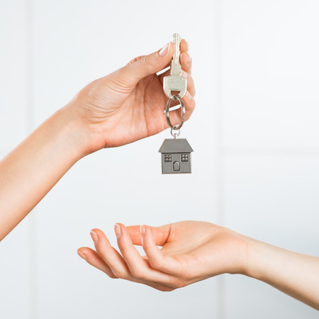 loans: Closeup shot of a female hand receiving house key. Woman buying new home. Close up hand holding house key. Stock Photo