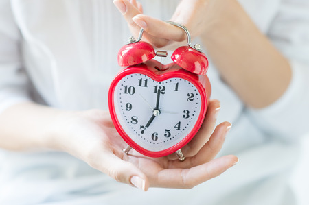 minute hand: Closeup shot of a woman holding red heartshape alarm clock. Time set at 7.00 am.  Close up of female hands holding a red alarm clock. Shallow depth of field with focus on the alarm clock. Stock Photo
