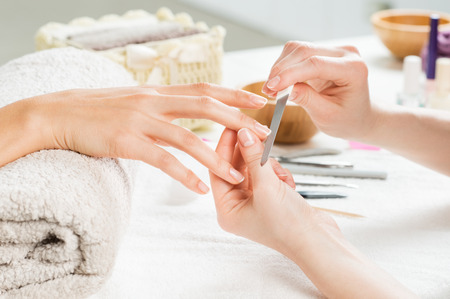 Closeup shot of a woman in a nail salon receiving a manicure by a beautician with nail file. Woman getting nail manicure. Beautician file nails to a customer. Shallow depth of field with focus on nailfile. Stock Photo