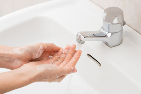 lather: Closeup shot of a woman washing hands with soap lather over bathroom sink. Girl cleaning hand.