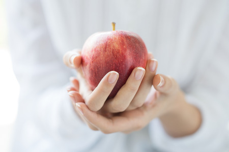 Closeup shot of a woman holding healthy red apple. Red apple in woman hands with white shirt at home. Shallow depth of field with focus on the red apple. Archivio Fotografico
