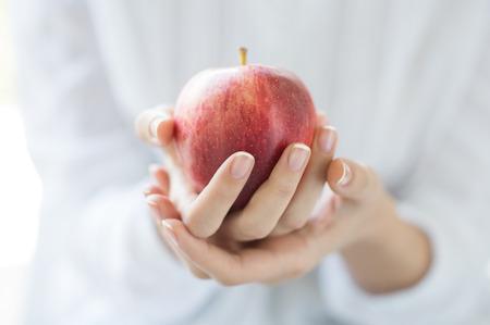 Gros plan d'une femme tenant la pomme rouge sain. Pomme rouge dans les mains de femme avec chemise blanche à la maison. Faible profondeur de champ avec un accent sur la pomme rouge. Banque d'images - 41263299